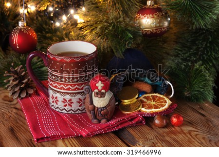 Cup of tea with chocolate Saint Nicholas and gift on a winter decor background - stock photo