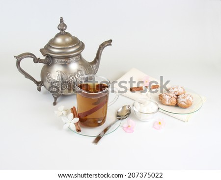 Cup of tea with cinnamon, silver teapot and almond cookies - stock photo
