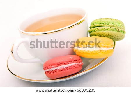 Cup of tea with colorful french macaron - stock photo