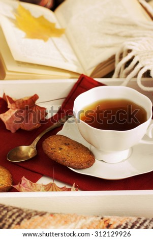 Cup of tea with cookies and autumn leaves