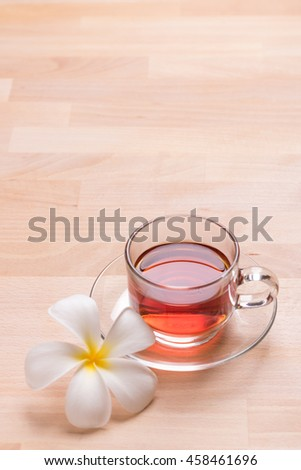 cup of tea with frangipani flower on wooden background
