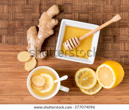 Cup of tea with fresh ginger root,  lemon and honey on wooden cutting board, natural remedy. - stock photo