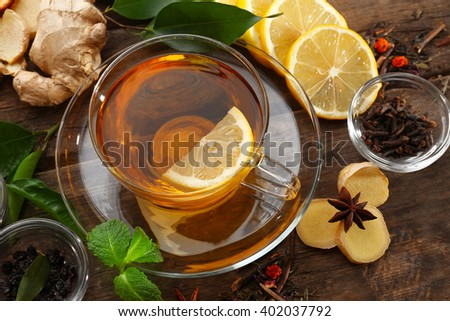 Cup of tea with ginger and cinnamon on wooden background - stock photo