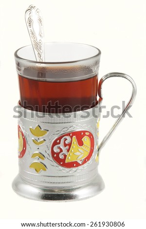 Cup of tea with glass-holder and spoon - stock photo