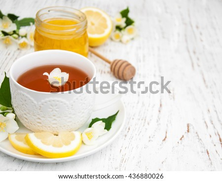 Cup of tea with jasmine flowers on a wooden background - stock photo