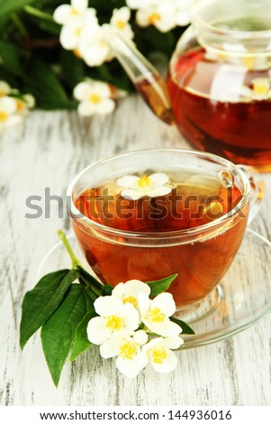 Cup of tea with jasmine, on wooden table, close-up - stock photo