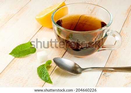 cup of tea with lemon and mint on a wooden tabl