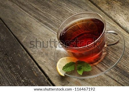 cup of tea with lemon and mint over wooden background - stock photo