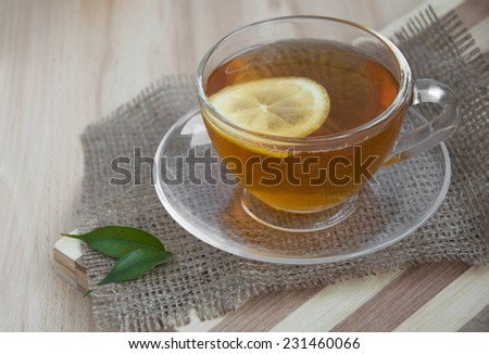 cup of tea with lemon over wooden background