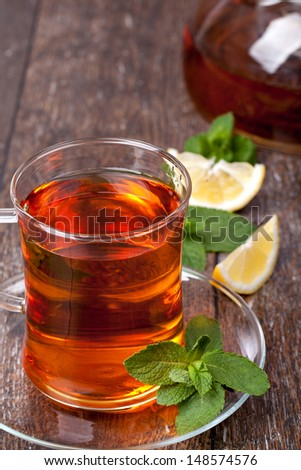 Cup of tea with mint and lemon on a wooden background