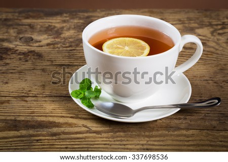 Cup of tea with mint leaf and lemon slice on old wooden desk, empty space for text