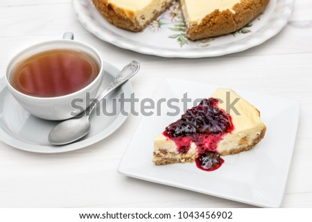 Cup of tea with piece of cheesecake with jam on the table.