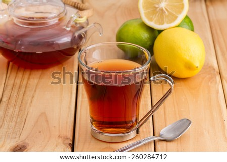 cup of tea with pot of tea and lime and lemons on a wooden kitchen table  - stock photo