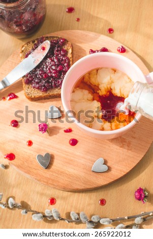 Cup of tea with pouring milk, homemade healthy bread with blackcurrant jam - homemade marmalade with fresh organic fruits from garden. rustic decoration, fruit jam on wooden table for breakfast. - stock photo