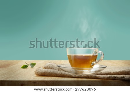 Cup of tea with sacking on the wooden table - stock photo