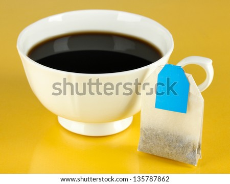 Cup of tea with tea bag on yellow background