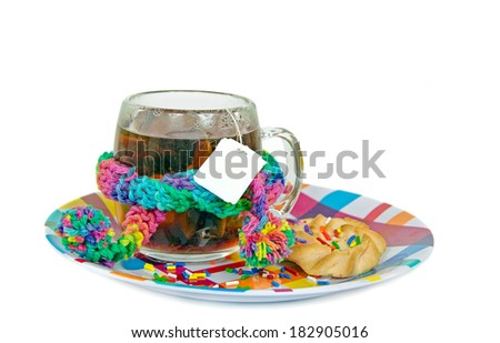 cup of tea with tea bag with winter scarf and shortbread cookies on colorful plate