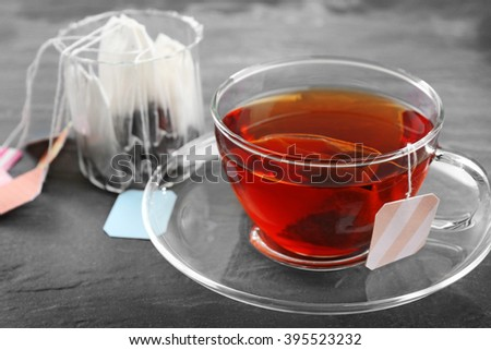Cup of tea with tea bags on grey background