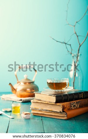 Cup of tea with teapot and vintage books on wooden table Blue background - stock photo
