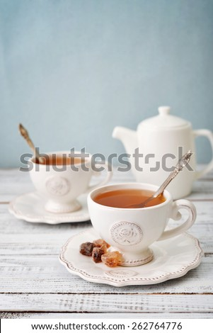 Cup of tea with teapot over blue background - stock photo