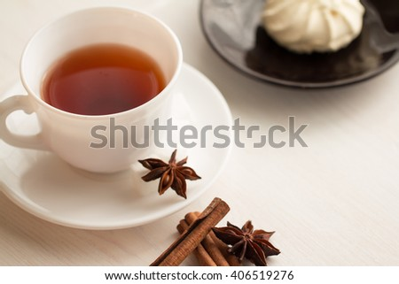 cup of tea with teaspoon, anise and marshmellow on saucer - stock photo