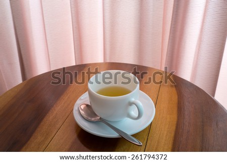 Cup of tea with teaspoon on the wooden table. - stock photo