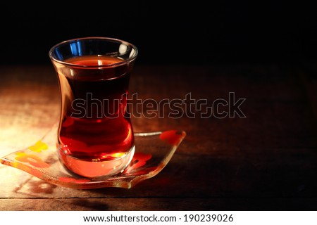 Cup of Turkish tea on saucer on dark background - stock photo