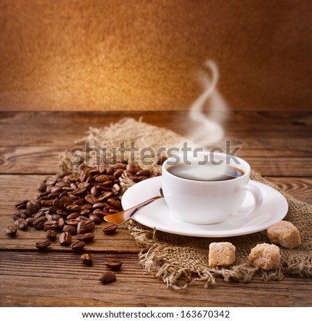 Cup of warm coffee, coffee beans and sugar cubes on  wooden surface. Free space for your text