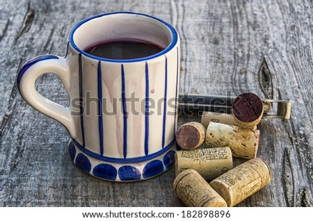 Cup of wine and a corkscrew with corks - stock photo