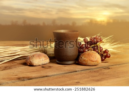 Cup of wine, bread. grapes and wheat on vintage table with warm sunset in background - stock photo