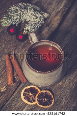Cup of winter tea on a wooden background