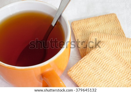 cup on saucer, biscuits and lemon - stock photo