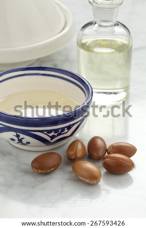 Cup with argan oil and nuts for cosmetics - stock photo