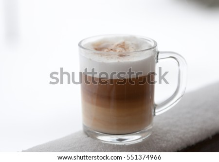 Cup with cappuccino coffee on the wooden bench covered with snow. Blurred winter background.