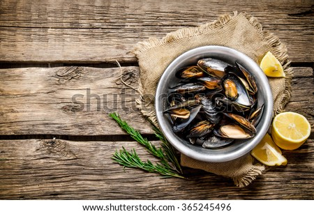 Cup with clams, Limon and rosemary. On a wooden table.  Free space for text . Top view - stock photo