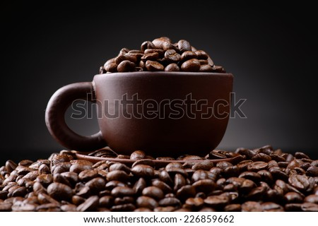 cup with coffee beans on a black background closeup