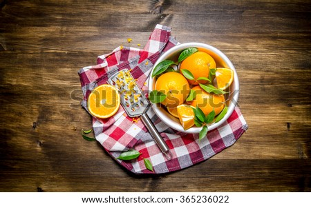 Cup with fresh oranges, zest and grater on fabric. On a wooden table. Top view - stock photo