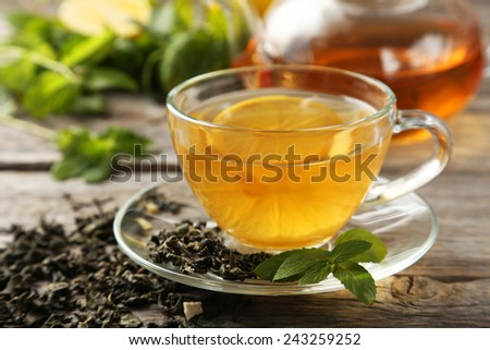 Cup with green tea and teapot on grey wooden background - stock photo