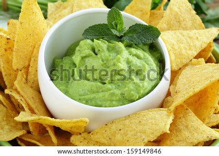 cup with guacamole and corn chips -  traditional Mexican appetizer - stock photo