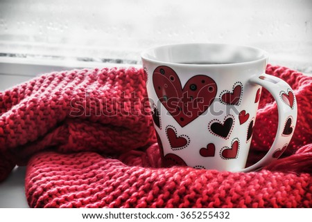 cup with hearts on the sill of a window. It can be used for Valentine's Day greetings - stock photo