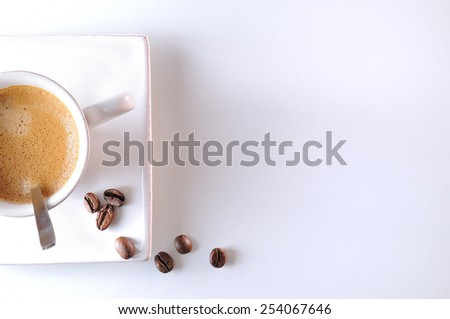 Cup with spoon and coffee beans on a white table top view - stock photo