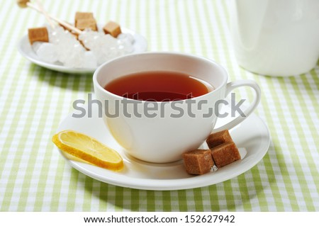 Cup with tea and lemon on green checkered background
