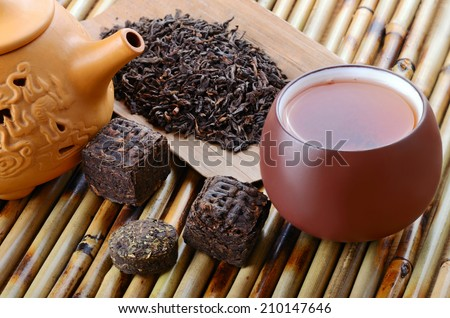 Cup with yellow teapot and various chinese black pu-erh tea leaves on bamboo mat background