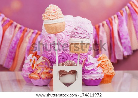 cupcake, cakepop and rosette cake on a white table with party festoon - stock photo