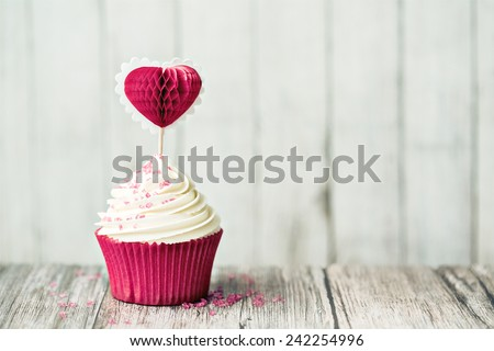 Cupcake decorated with a heart shaped cake pick - stock photo