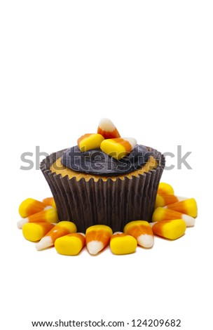 Cupcake decorated with candy corn and chocolate cream displayed on white. - stock photo