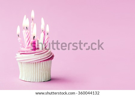 Cupcake decorated with pink birthday candles - stock photo
