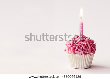 Cupcake decorated with pink chocolate curls and a single candle - stock photo
