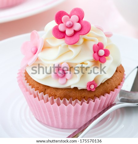 Cupcake decorated with pink fondant flowers - stock photo