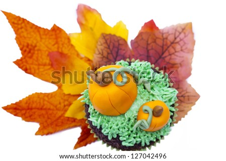 Cupcake decorated with pumpkin miniature and autumn leaves over white background. - stock photo